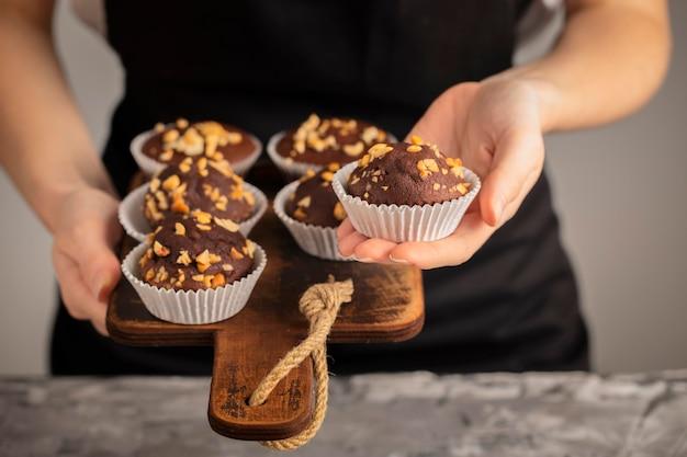 Persona de vista frontal sosteniendo cupcakes dulces Foto gratis