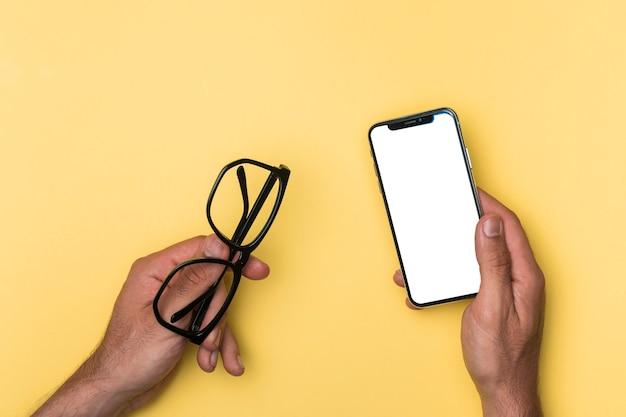 Persona vista superior que sostiene el teléfono inteligente maqueta Foto gratis