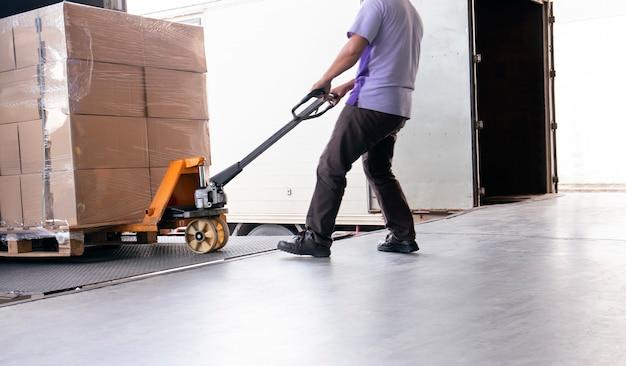 El personal del almacén arrastra la transpaleta manual o la carretilla elevadora manual con la paleta de envío Foto Premium