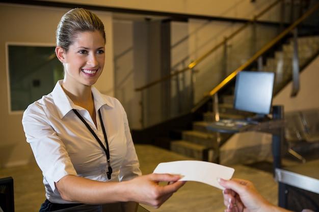 Personal femenino dando boleto al pasajero Foto gratis