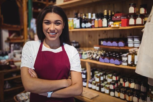 Personal femenino de pie con los brazos cruzados en el supermercado Foto gratis
