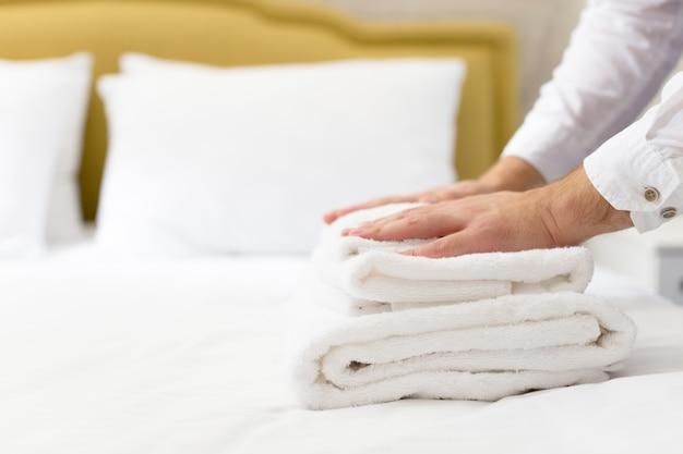 El personal del hotel coloca la almohada en la cama Foto Premium