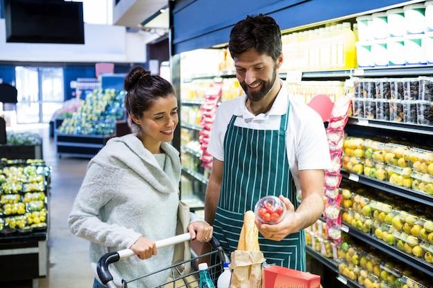 Personal masculino sonriente que ayuda a una mujer con compras Foto Premium