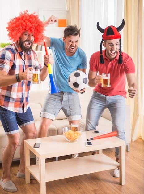 Las personas con atuendos ven fútbol y animan al equipo. Foto Premium