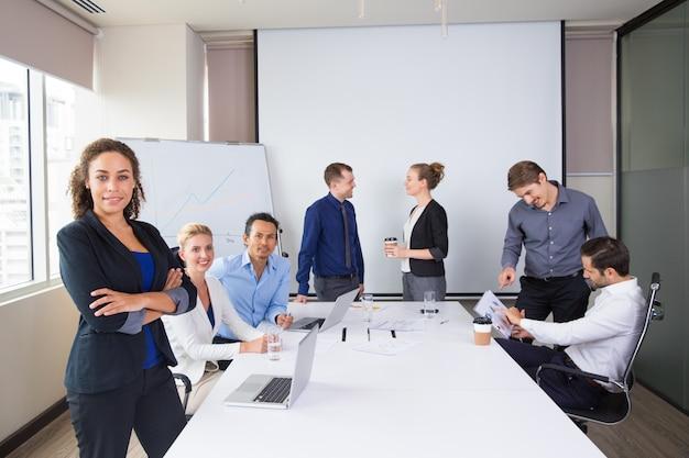 Personas de negocios posando sonrientes en una sala de reuniones Foto Gratis