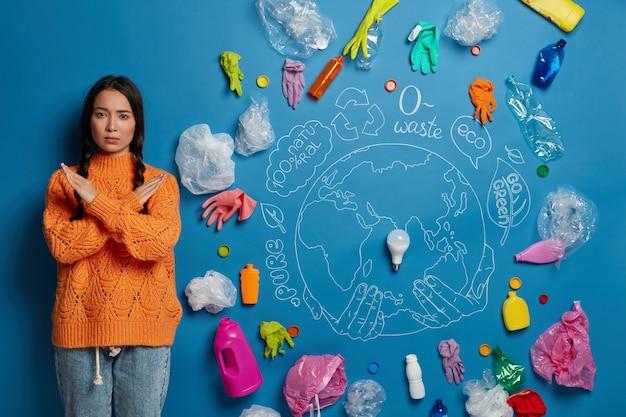 Personas, ecología, prohibición, concepto de rechazo. chica asiática seria mantiene los brazos cruzados sobre el pecho, dice no al plástico, es ecológica, se apoya contra la pared azul Foto gratis