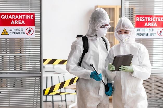 Personas en equipo de protección desinfectando un área peligrosa Foto gratis
