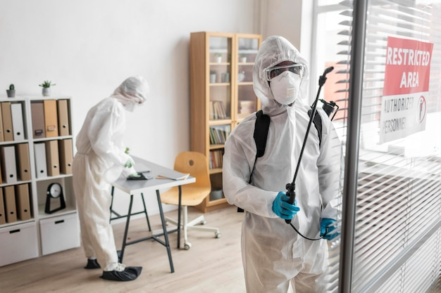 Personas con equipo de protección para desinfectar un área peligrosa Foto gratis