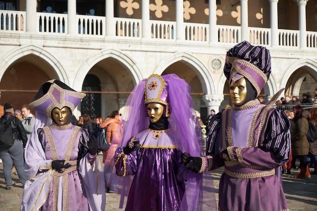 Personas con máscaras y disfraces en el carnaval de venecia. Foto Premium