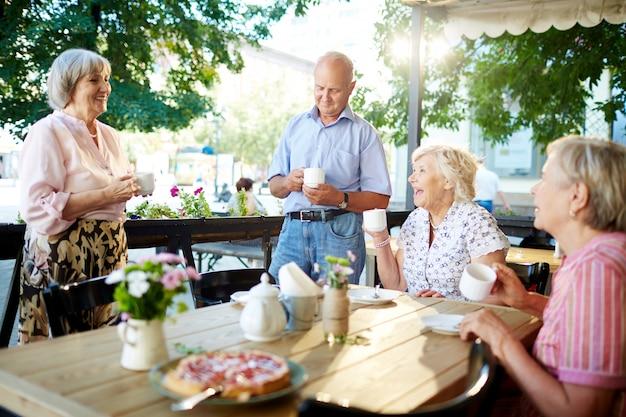 Personas mayores celebrando vacaciones en café Foto gratis