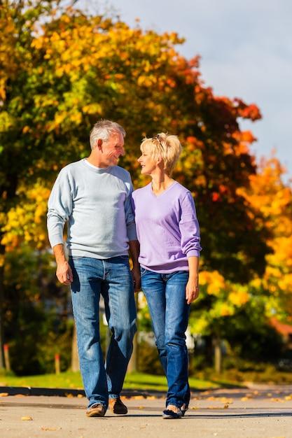 Personas mayores en otoño o otoño caminando de la mano Foto Premium