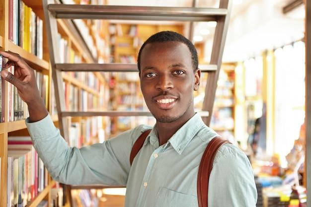 Personas, ocio y educación. estudiante afroamericano curioso que busca un libro en la biblioteca mientras investiga. turista negro que elige el libro de frases del estante en la librería durante las vacaciones en el extranjero Foto gratis