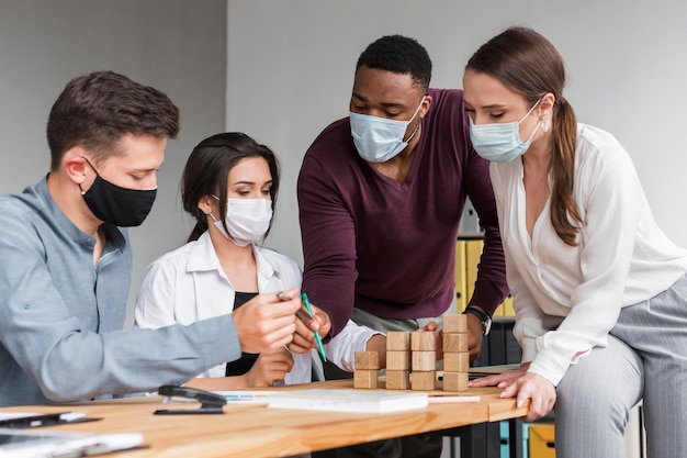 Personas en la oficina durante una pandemia que tienen una reunión con máscaras Foto gratis