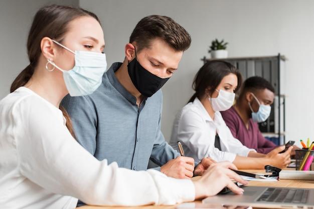 Personas en la oficina que trabajan durante una pandemia con máscaras Foto gratis