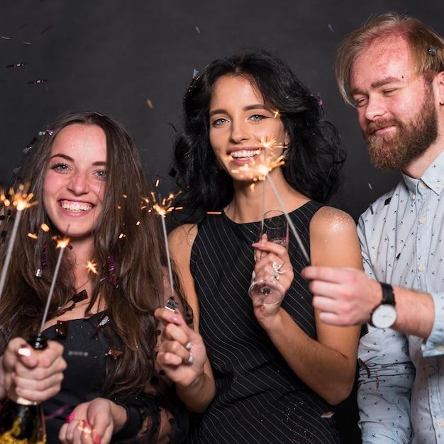 Personas de pie con bengalas en fiesta Foto gratis