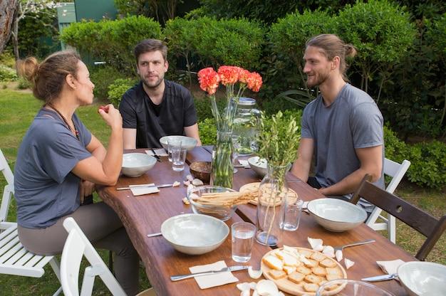 Personas positivas que tienen comida en la mesa de madera en el patio trasero Foto gratis