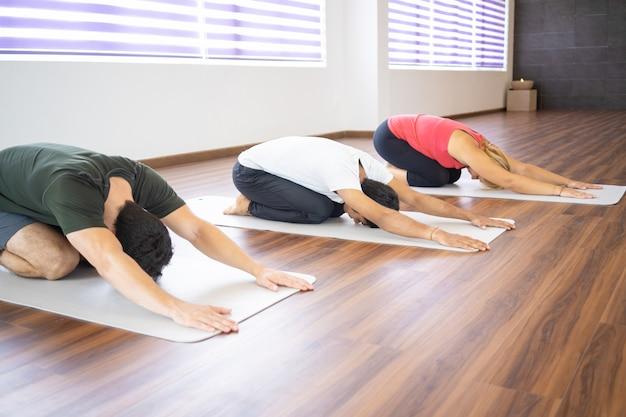 Las personas que hacen al niño posan en la clase de yoga