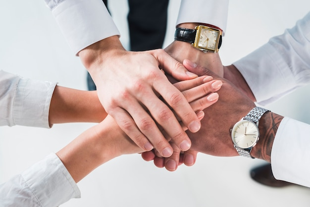 Las personas que ponen las manos apiladas prometen ayuda y apoyo contra el fondo blanco Foto gratis