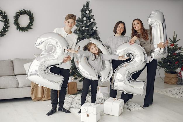 Personas que se preparan para navidad. personas con globos 2021 / familia descansando en una sala festiva. Foto gratis