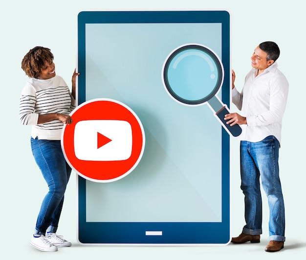 Personas que tienen un icono de youtube y una tableta. Foto gratis