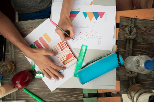 Personas que trabajan con diagramas y gráficos en mesa. Foto gratis