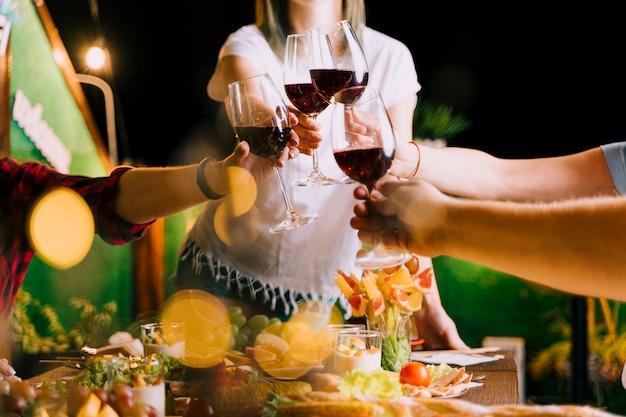 Las personas que tuestan vino en la fiesta de tiro medio Foto gratis