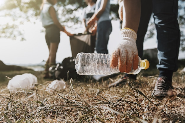 Personas recogiendo basura y poniéndola en una bolsa negra de plástico para limpiar Foto Premium
