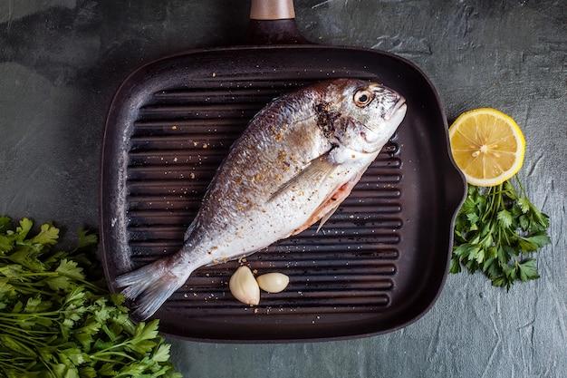 Pescado dorado crudo con especias y limón. vista superior Foto Premium