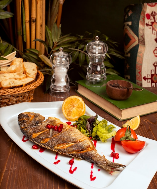 Pescado entero a la plancha con salsa amarilla, ensalada de verduras, limón y semillas de granada en un plato blanco Foto gratis