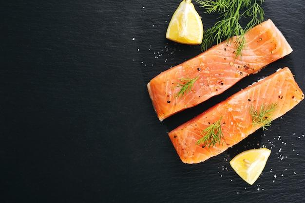 Pescado de salmón crudo en pizarra negra Foto gratis