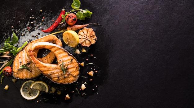 Pescado salmón a la plancha con condimento y diversas verduras sobre fondo de piedra negra Foto Premium