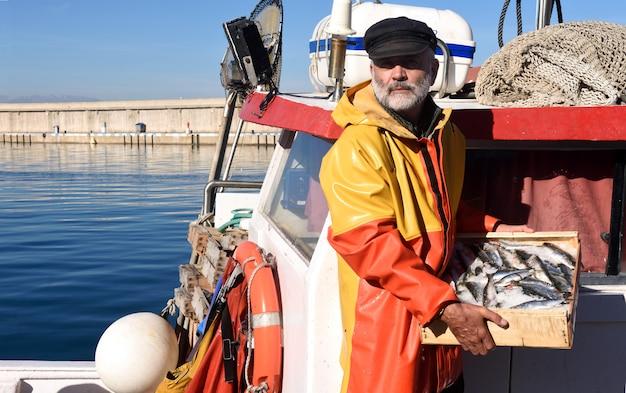 Pescador con una caja de peces dentro de un barco de pesca Foto Premium