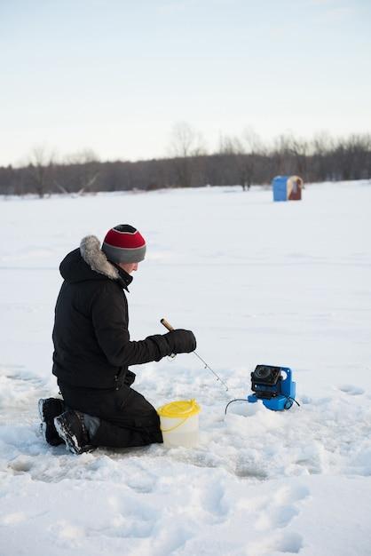 Pescador de hielo pescando en paisaje nevado Foto gratis