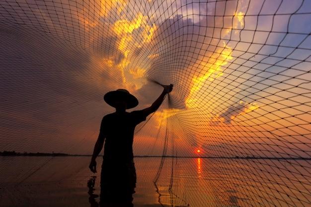 Pescador de silueta con puesta de sol Foto Premium