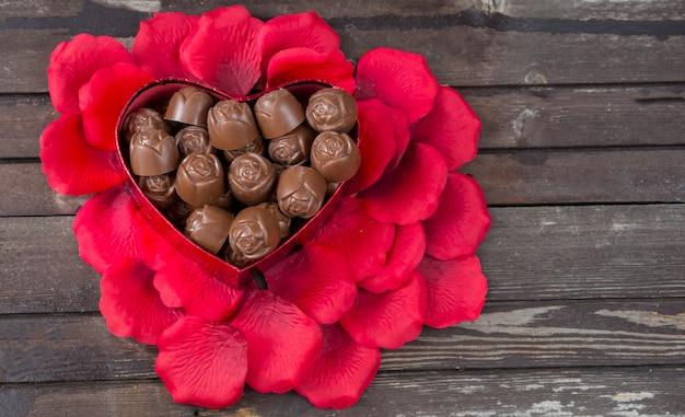Pétalos de rosa, dulces en forma de corazón sobre un fondo de madera oscuro Foto Premium