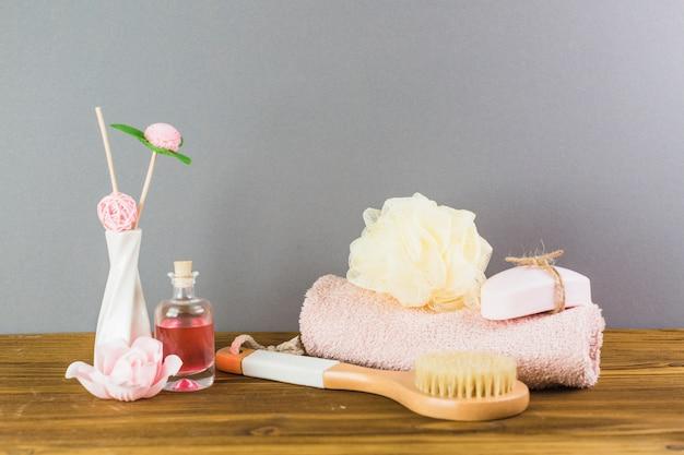Petróleo; cepillo; toalla; loofah y jabón en tablero de madera Foto gratis