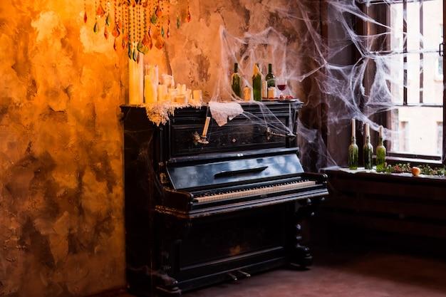 Piano de pie cerca de la ventana. eerie cobweb cubrió botellas con velas y candelabros en un entorno de casa embrujada. interior y decoraciones para fiesta de halloween. granada fresca madura, casa embrujada Foto Premium