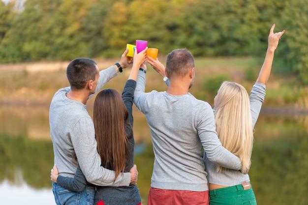 Picnic con amigos en el lago cerca de la tienda de campaña. amigos de la empresa con caminata naturaleza picnic. excursionistas relajantes durante el tiempo de bebida. picnic de verano tiempo de diversión con amigos. Foto Premium