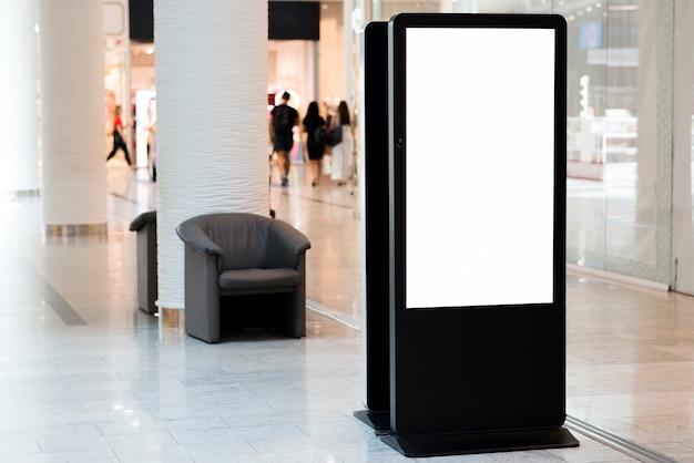 De pie cartelera en blanco dentro de centro comercial Foto gratis