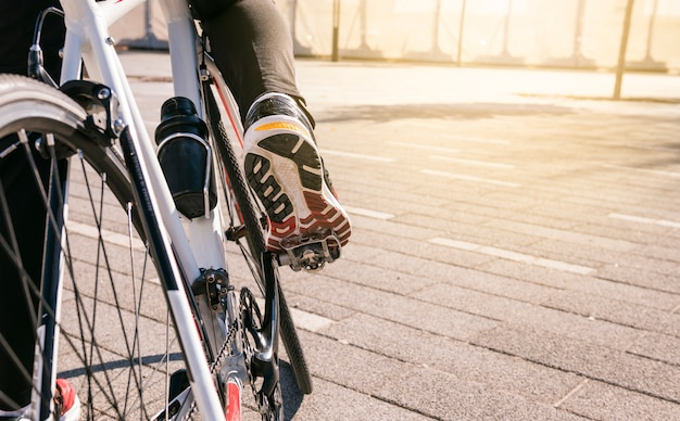 Pie de ciclista masculino en bicicleta pedaleando bicicleta al aire libre Foto gratis