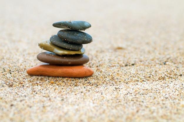 Piedras en equilibrio en un playa de arena Foto gratis