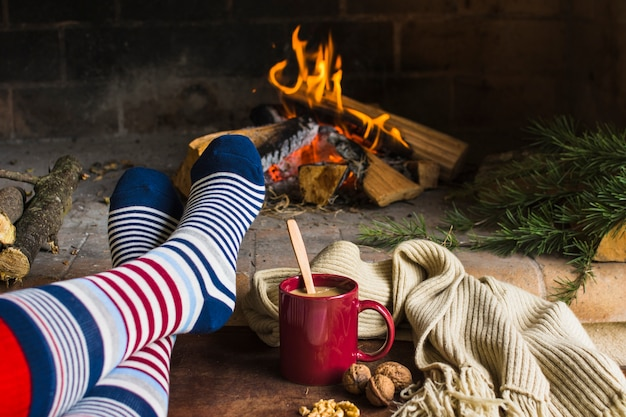 Piernas en calcetines cerca de la chimenea Foto gratis
