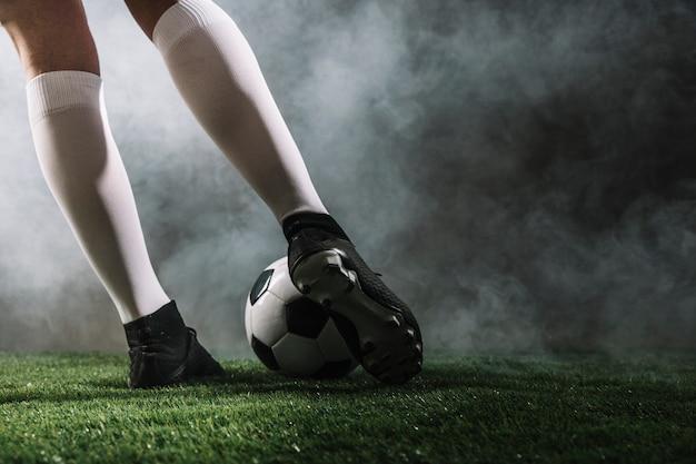 Piernas de cultivo que disparan el balón de fútbol  a782de7ecfa76