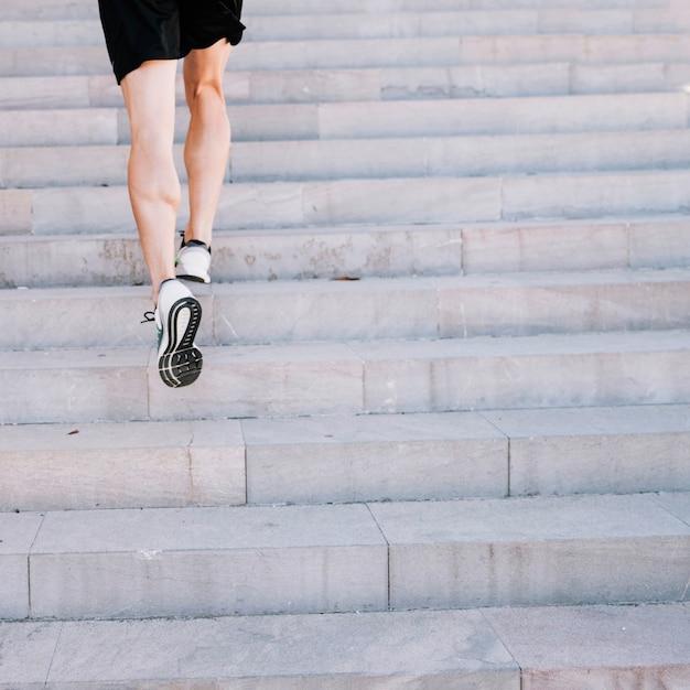 Piernas de cultivos corriendo en las escaleras Foto gratis