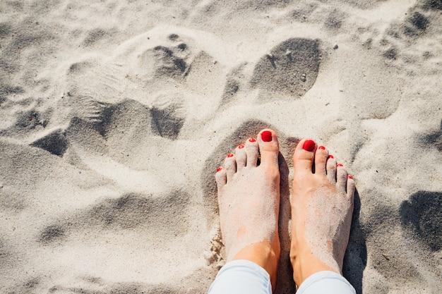 Piernas femeninas descalzos en la arena de la playa, vista desde arriba Foto Premium