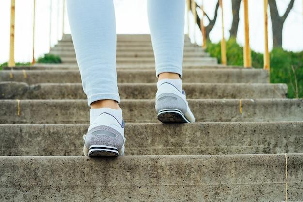Piernas femeninas en jeans y zapatillas de deporte, subir las escaleras de concreto al aire libre Foto Premium