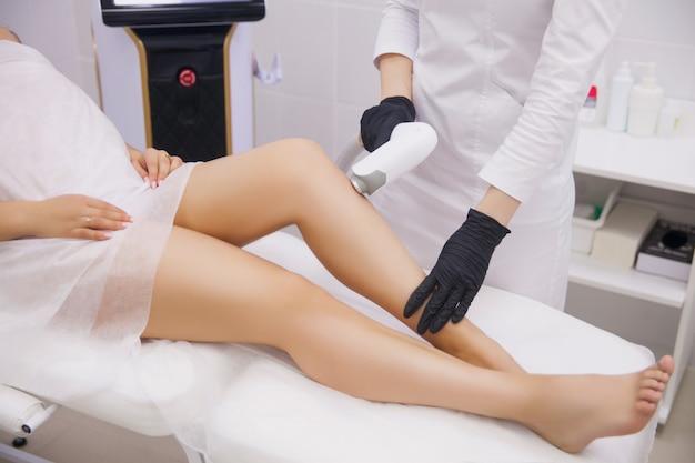 Piernas femeninas, mujer en clínica de belleza profesional durante la depilación láser Foto Premium