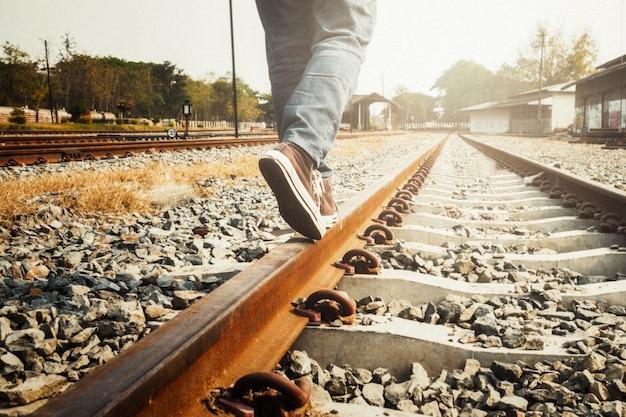 Piernas femeninas en zapatillas de deporte en el carril del ferrocarril. Foto gratis