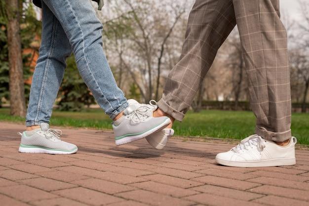 Piernas De Hombre Y Mujer Joven En Pantalones Y Calzado Deportivo Haciendo Golpe De Pie En La Carretera En El Parque Publico Foto Premium