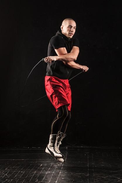 Las piernas del hombre musculoso con saltar la cuerda Foto gratis